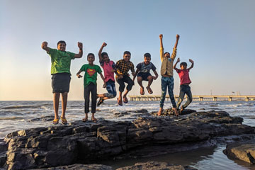 Kids jumping on a rock